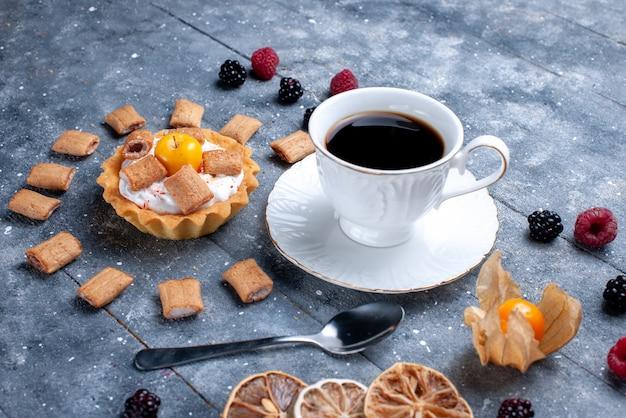 Tasse kaffee mit cremigem kuchenkissen bildete kekse zusammen mit beeren auf grauem schreibtisch, beerenkeksplätzchen
