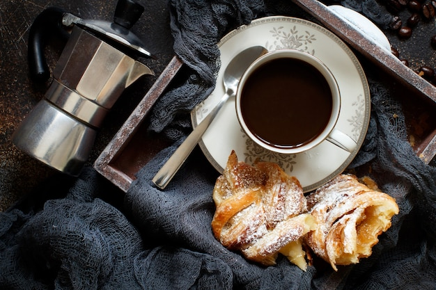 Tasse kaffee mit croissant auf einem dunklen hintergrund draufsicht