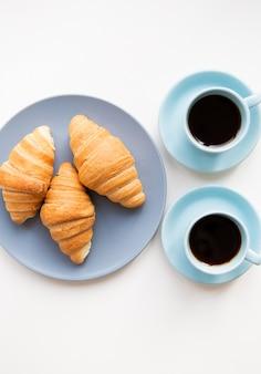 Tasse kaffee mit croissant auf weißem hintergrund