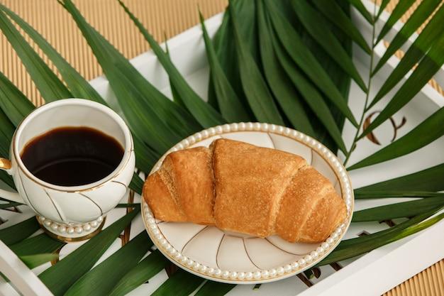 Tasse kaffee mit croissant auf weißem tablett mit farnblatt am morgen. gesundes essen