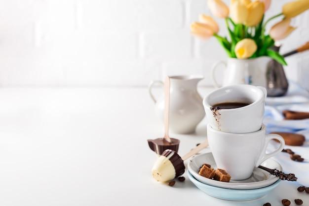 Tasse kaffee mit den gelben tulpen lokalisiert auf weißem hintergrund.