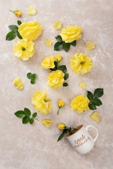 Tasse kaffee mit der aufschrift guten morgen und gelbe rosen und blätter