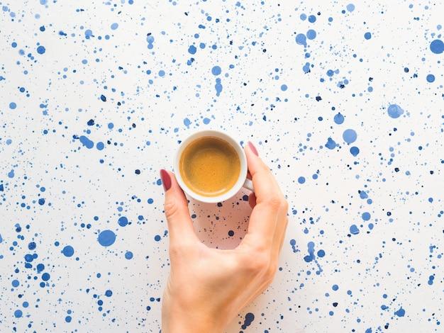 Tasse kaffee mit der hand der frau. flach liegen