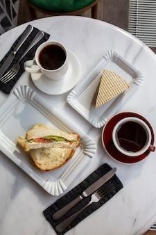 Tasse kaffee mit dessert auf dem marmortisch. kaffeetag. frühstück auf weißem grund. heißes getränk mit kuchen. draufsicht auf aromatischen kaffee. schwarzer kaffee zum essen. frühstück in einem café. tag des essens