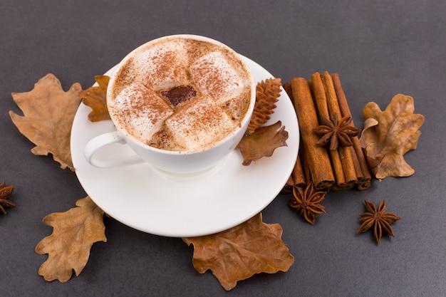 Tasse kaffee mit eibischen und kakao, blättern, getrockneten orangen, zimt und sternanis, grauer steinhintergrund. leckeres heißes herbstgetränk. copyspace.