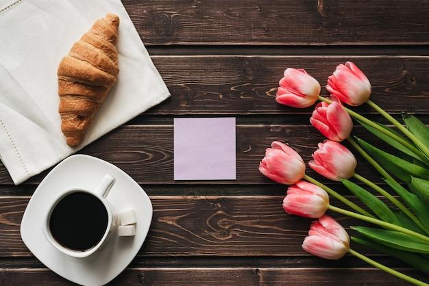 Tasse kaffee mit einem blumenstrauß von rosa tulpenblumen und einem hörnchen für das morgenfrühstück