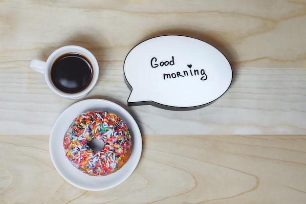 Tasse kaffee mit einem donut und einer platte auf einem holzbeschaffenheitshintergrund. konzept zum thema guten morgen.