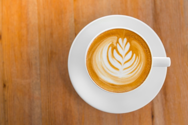 Tasse kaffee mit einem hauch von weizen in den schaum gezogen, von oben gesehen