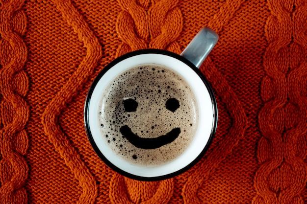 Tasse kaffee mit einem lächeln auf einem gestrickten