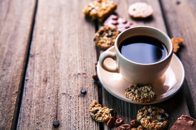 Tasse kaffee mit einer köstlichen schokolade und keksen auf einem hölzernen hintergrund
