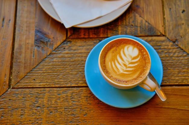 Tasse kaffee mit einer weißen blumendekoration auf eine holzoberfläche gestellt