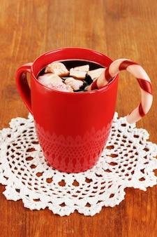 Tasse kaffee mit feiertagssüßigkeiten auf holztischnahaufnahme
