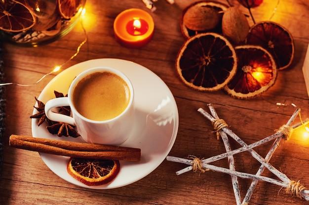 Tasse kaffee mit festlichen dekorationen und feenhaften girlandenlichtern