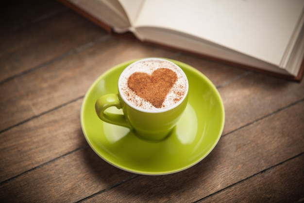 Tasse kaffee mit formherz und buch auf einem holztisch