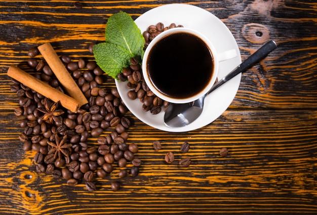 Tasse kaffee mit gerösteten bohnen und gewürzen
