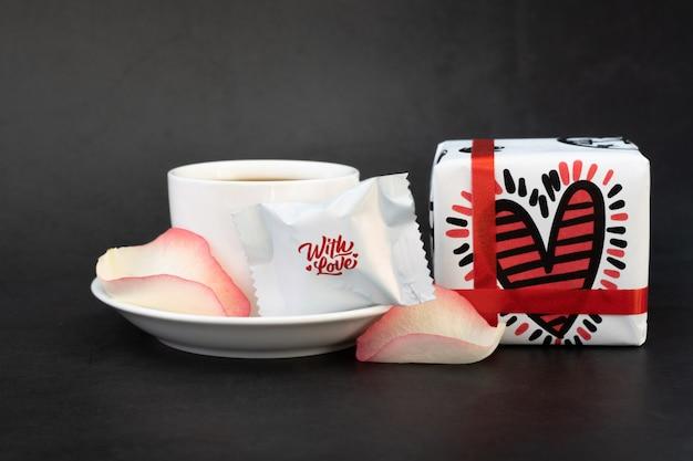 Tasse kaffee mit geschenken, süßigkeiten und rosenblättern.