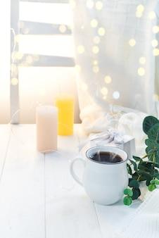 Tasse kaffee mit gestricktem schal beim bleiben auf hölzernem behälter im bett, kopienraum. guten morgen frühstück