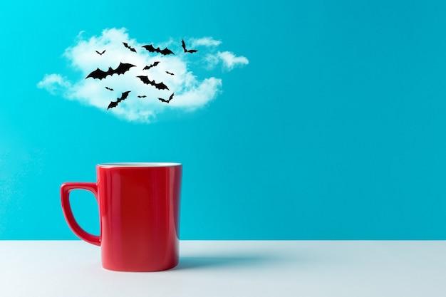 Tasse kaffee mit halloween fledermausdekorationen