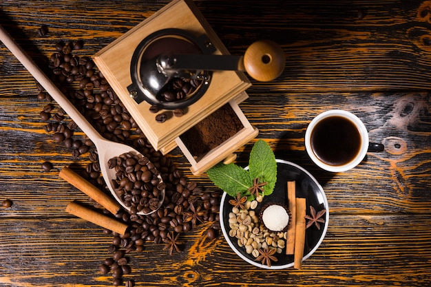 Tasse kaffee mit handmühle, bohnen und gewürzen