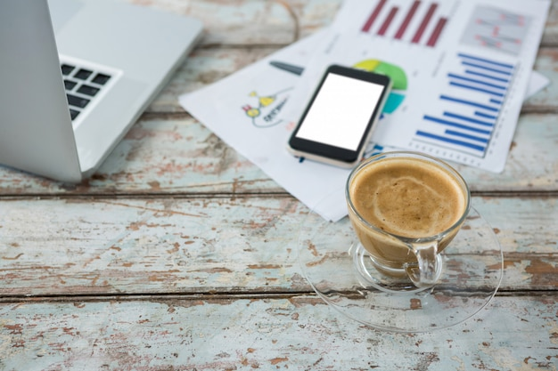 Tasse kaffee mit handy, grafik und laptop