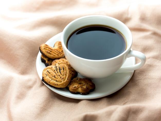 Tasse kaffee mit hausgemachten keksen auf den bettdecken,