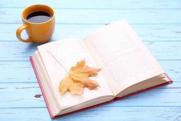 Tasse kaffee mit herbstblatt und buch auf hölzernem hintergrund