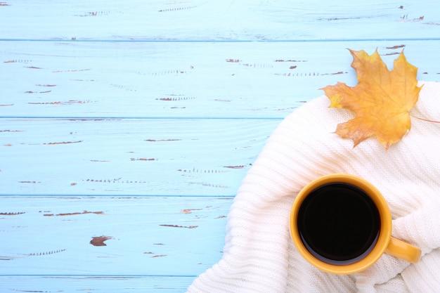 Tasse kaffee mit herbstblatt und -strickjacke auf hölzernem hintergrund