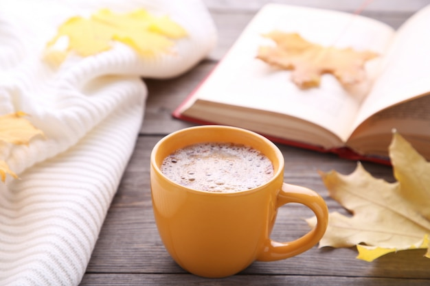 Tasse kaffee mit herbstlaub und altem buch auf hölzernem hintergrund