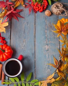 Tasse kaffee mit herbstlaub und kleinen kürbisen
