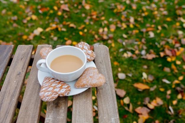 Tasse kaffee mit herzformplätzchen auf einem tisch in der herbstsaisonzeit
