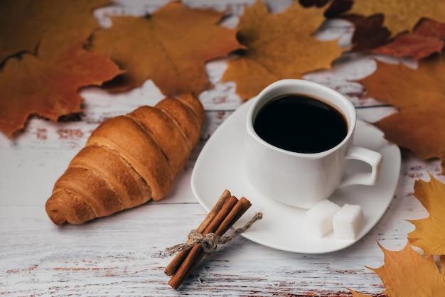 Tasse kaffee mit hörnchen und zimtstangen auf einem holztisch