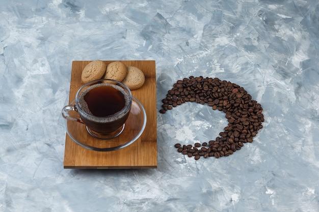 Tasse kaffee mit hohem blickwinkel, kekse auf holzschneidebrett mit kaffeebohnen auf hellblauem marmorhintergrund. horizontal