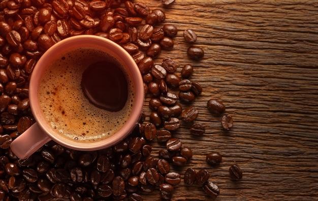 Tasse kaffee mit kaffeebohnen auf hölzernem hintergrund des schmutzes.