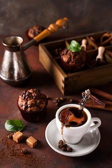 Tasse kaffee mit kaffeebohnen, holzkiste mit körnern des kaffees und gewürzen, kleiner kuchen