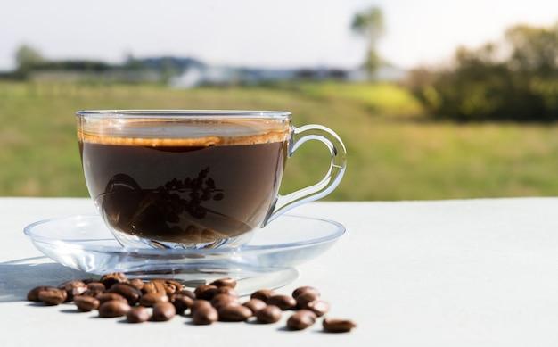 Tasse kaffee mit kaffeebohnen im freien