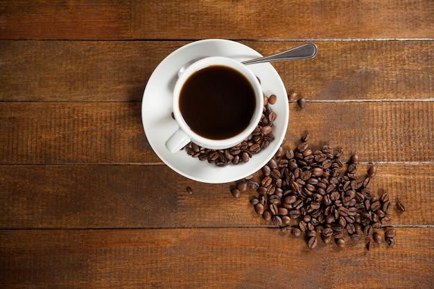 Tasse kaffee mit kaffeebohnen und löffel
