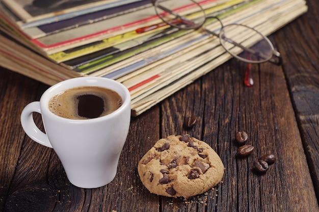 Tasse kaffee mit keks und alten zeitschriften auf holztisch