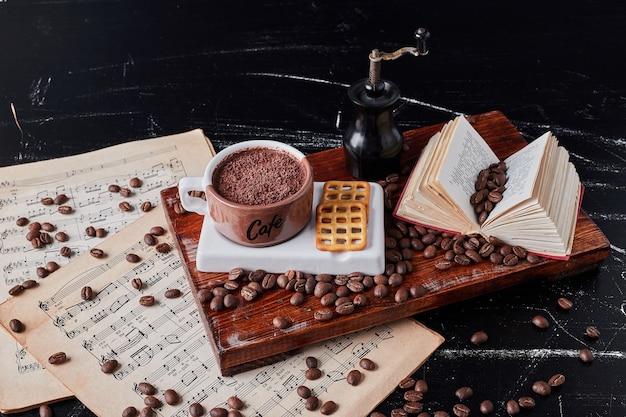 Tasse kaffee mit keksen auf einem holzbrett.