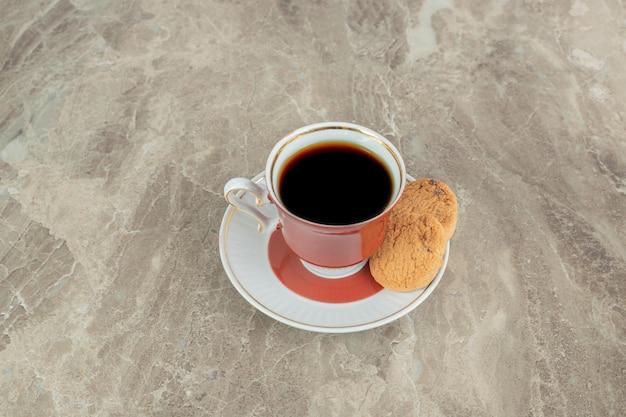 Tasse kaffee mit keksen auf marmoroberfläche