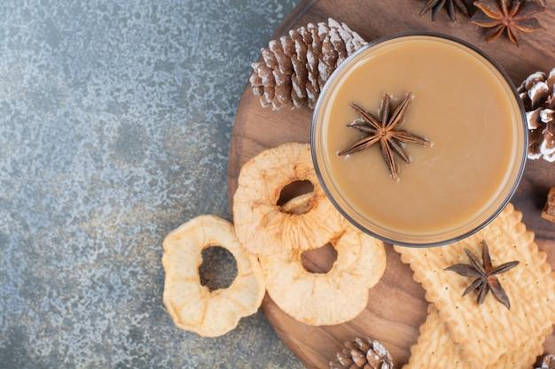 Tasse kaffee mit keksen und tannenzapfen auf holzteller. hochwertiges foto