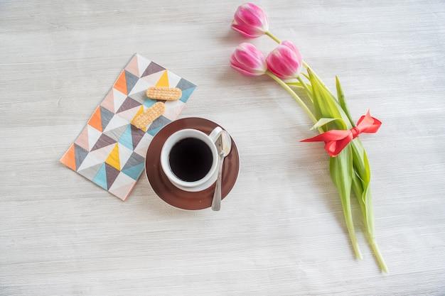 Tasse kaffee mit keksen und tulpen, romantisches frühstück