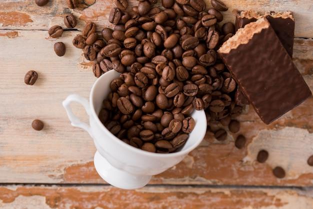 Tasse kaffee mit körnern zerstreute auf einen hölzernen hintergrund. schokoladenwaffel, süßer nachtisch