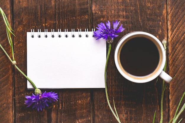 Tasse kaffee mit kornblumen. ansicht von oben. kaffee und blume. kopieren sie platz