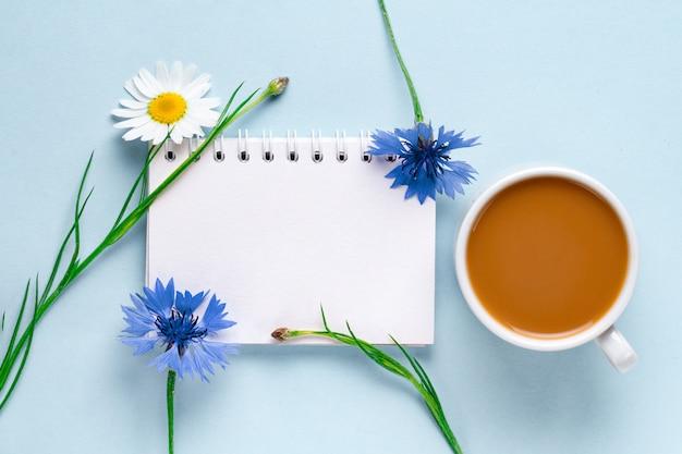 Tasse kaffee mit kornblumen und kamille. ansicht von oben. kaffee und blume.