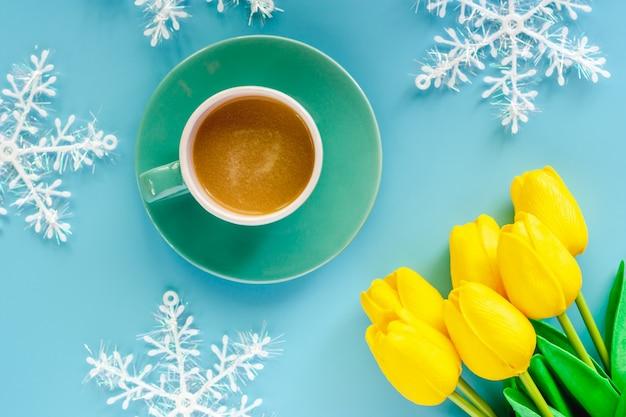Tasse kaffee mit künstlichen gelben tulpen und schneeflockenverzierungen auf blauem hintergrund