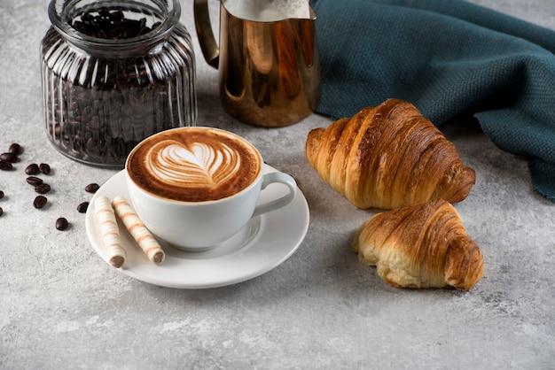 Tasse kaffee mit lattekunst. mit zwei leckeren croistant duper