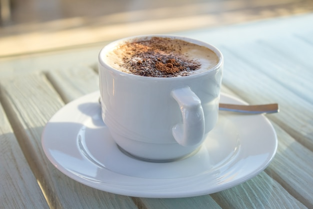 Tasse kaffee mit lattekunst von kardamom auf hölzerner weißer tabelle.