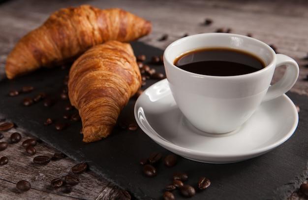 Tasse kaffee mit leckerem gebäck und gestreuten kaffeebohnen. morgensnack.