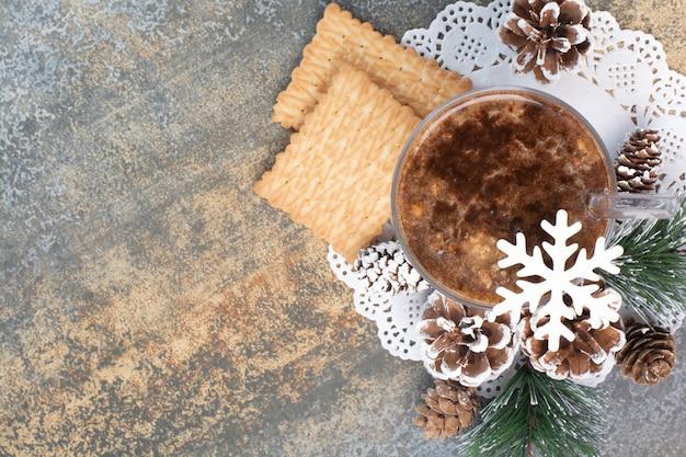 Tasse kaffee mit leckeren crackern und tannenzapfen auf marmorhintergrund. hochwertiges foto