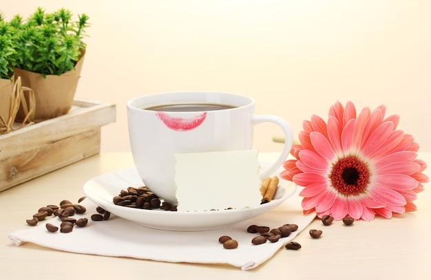 Tasse kaffee mit lippenstift und gerberabohnen, zimtstangen auf holztisch